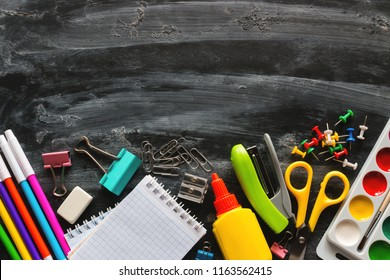 school supplies on a blackboard with space for text. school education concepts