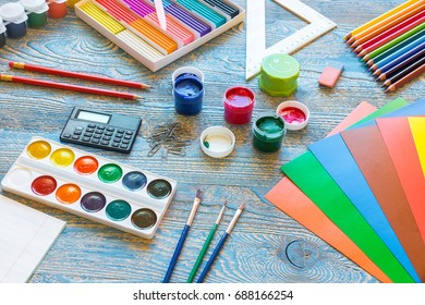 School supplies on a blue background, paints and brushes