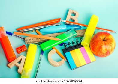 school supplies on a bright blue background, top view, concept of education, creative disorder, desktop, school desk