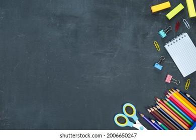 Schulbedarf auf dunklem Hintergrund. Zurück zum Schulkonzept. Draufsicht, Textraum