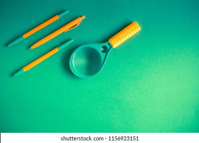 School supplies on green background ready for your design. pencils, magnifying glass, pens. Back to school. Flat lay, top view, copy space