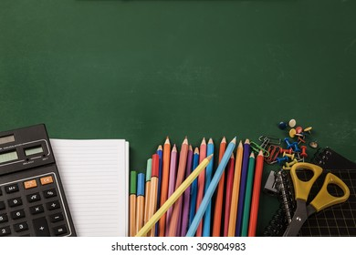 School supplies on green board background. Back to school.