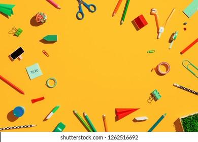 School supplies on orange background. Back to school, creative concept flat design.
