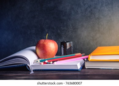 School supplies are on the table. Books, pencils and apples is a collection of the student. The concept of school and education