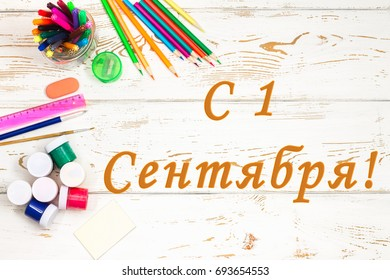 """School supplies on a white wooden background with the inscription in Russian """"On September 1!"""""""