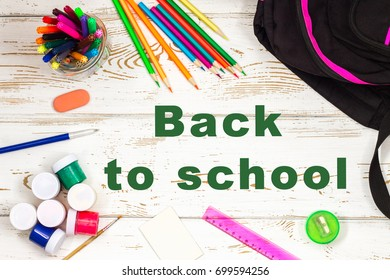 School supplies on a white wooden background with an empty space for inscriptions