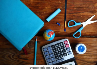 School supplies on wooden background. Flat lay photo with daybook, calculator and pencils