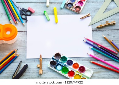 school supplies on a wooden background, photo in flatlay style. Paint, pencils, ruler, scissors, notepad, colored pencils, stapler