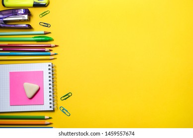 School supplies on yellow background. Top view. Copy space.