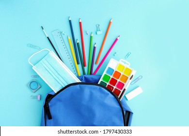 School supplies and a protective medical mask poured out of a blue backpack or knapsack on a light background, top view. Back to school, study after vacation and quarantine. Place for text