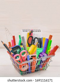 School supplies in a shopping basket, natural wood background. Back to school concept
