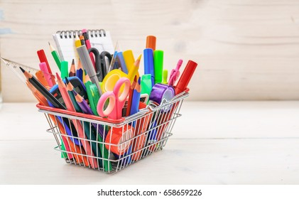 School supplies in a shopping basket on white background