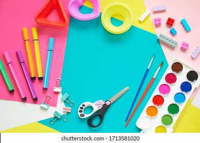 School supplies, stationery on blue background - space for caption. Child ready to draw with pencils and make application of colored paper. Top view.