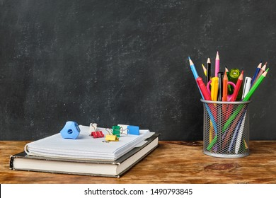 School supplies such as textbook, notebook, pens, pencils, scissors over chalkboard background
