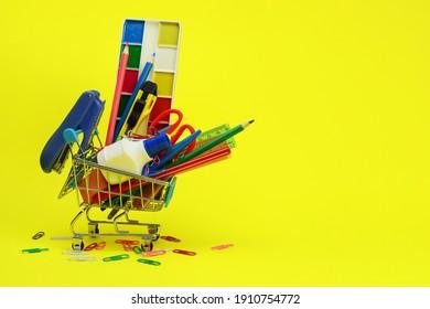 school supplies in supermarket trolley on yellow background
