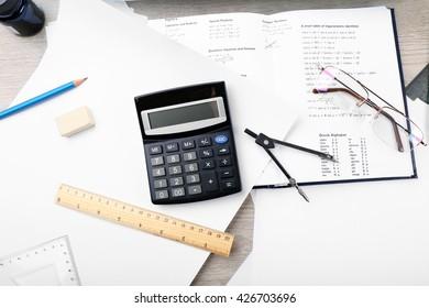 School supplies and textbook on mathematics close up