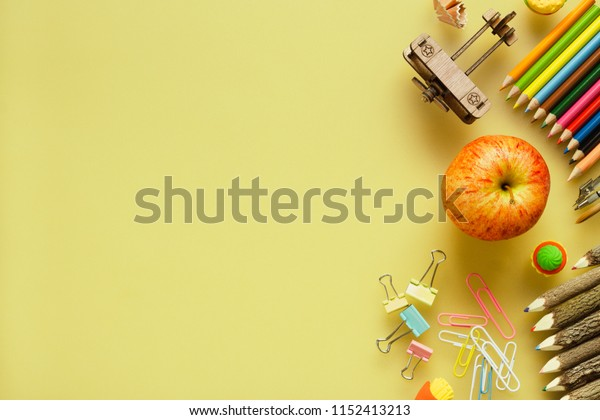 School supplies, toys and apples on yellow background. ideals for back to school background.