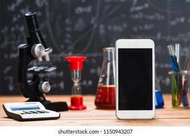 School supplies. Tubes with chemical liquids stand on a wooden table on a chalkboard background with digital formulas
