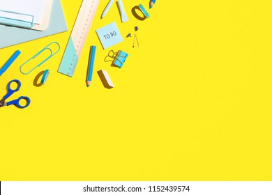 School supplies at yellow background. Back to school creative flat lay desk.