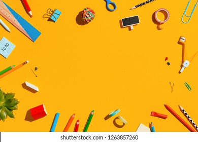 School suppplies and paper notebook on a blue table. Back to school creative illustration, flat lay.