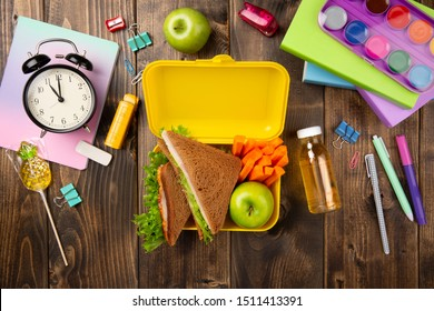 School table with books, alarm, pens, notebook and yellow lunch box with food and juice on wood background top view. Sandwich, apple and carrot slice.
