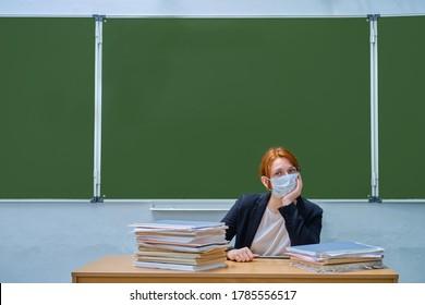 Schullehrer in medizinischer Maske auf grünem Schulboardhintergrund, Kopienraum. Frauenlehrerin mit rotem Haar sitzt an einem Schreibtisch mit Büchern. Konzept des Schulabgrenzungsproblems