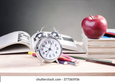 A school teacher's desk with stack of exercise books colored pencils and red apple. A green blackboard