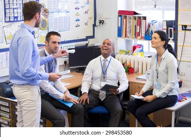 School teachers gather in a small school office for a chat. They look happy. A woman and three men group together.