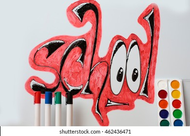 school text word painted graffiti red and black color with smiley eyes near four markers or pens and paint palette on white background