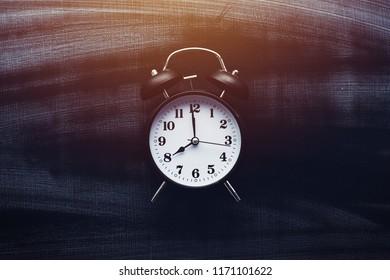 It is school time, alarm clock on blackboard