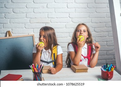 School time of girls. Friendship of small sisters in classroom at knowledge day. Happy school kids at lesson in september 1. Back to school and home schooling. Little girls eat apple at lunch break.