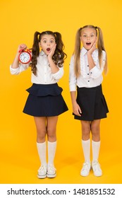 School time. Surprised shocked kids hold alarm clock counting time. Latecomer will be punished. It is time. School schedule. Schoolgirls and alarm clock. Children school pupils. Knowledge day.
