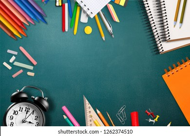 It is school time, top view flat lay of vintage alarm clock, chalk and books on blackboard surface as copy space