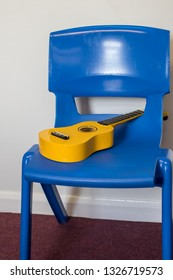 School ukulele lesson. Yellow uke left in music room. Musical instrument on blue plastic chair.