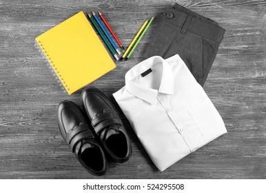 School uniform and accessories on wooden background