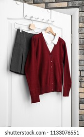 School uniform for girl hanging on white door