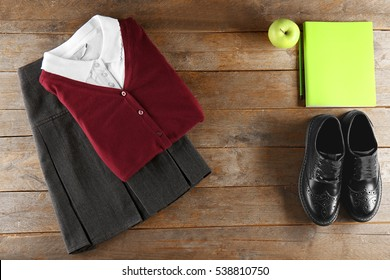 School uniform on wooden background, flat lay