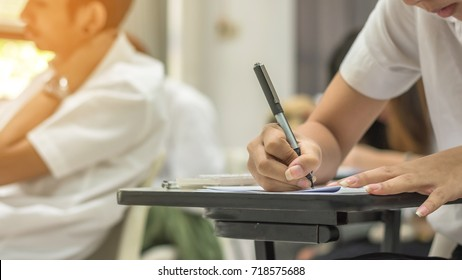 School or univeristy student studying taking note or having exam in classroom for education and literacy concept