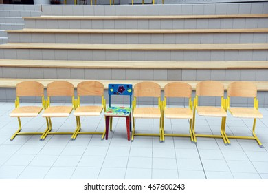 School wooden chairs in a row with one colored chair sticking out.