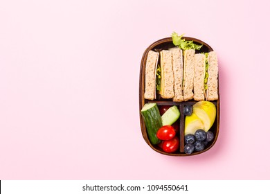School wooden lunch box with sandwiches, vegetables, , tomatoes and fruits on pink background. Healthy children eating concept flat lay. Top view with copy space.