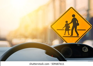 School zone warning sign and inside car view ,steering wheel on blur traffic road with colorful bokeh light abstract background. Copy space of transportation and travel concept. Vintage tone color.