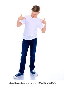 A school-age boy points his fingers at his white T-shirt, on which you can make any inscription. The concept of advertising products, clothing design. Isolated on white background.