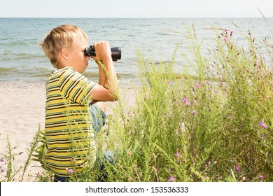 A school-aged boy looks through binoculars with a sea shore on the background
