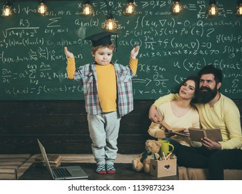 Schoolboy answer lesson at chalkboard. Little schoolboy in graduation cap. Schoolboy and family in classroom. Man and woman listen to schoolboy. I know the answer.