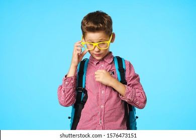 Schoolboy with a backpack on his back glasses learning studio childhood education