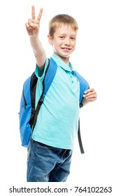 schoolboy with backpack smiling and showing a hand gesture on a white background isolated