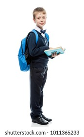 schoolboy with a book and a backpack in the studio on a white background in full length isolated