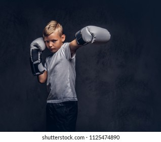 Schoolboy boxer with blonde hair dressed in a white t-shirt wearing boxing gloves shows a boxing kick. Isolated on a dark textured background.
