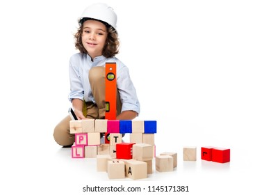 schoolboy in costume of architect and helmet measuring wooden cubes with spirit level isolated on white