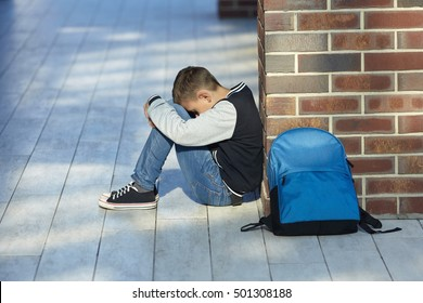 schoolboy crying in the hallway of the school, negative emotion